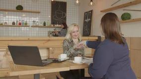Apretón de manos de las empresarias que hace trato en café almacen de metraje de vídeo