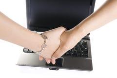 Apretón de manos sobre la computadora portátil Imagen de archivo libre de regalías