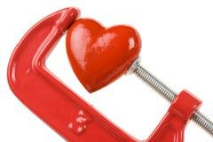 Apretón del tornillo y corazón rojo Fotos de archivo libres de regalías