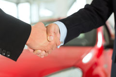 Apretón de manos de dos hombres en juegos con un coche rojo Fotos de archivo
