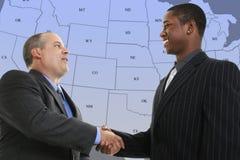 Apretón de manos de los hombres de negocios delante de la correspondencia azul del estado de los E.E.U.U. Imagenes de archivo
