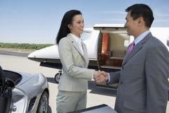 Apretón de manos del negocio en el campo de aviación Imágenes de archivo libres de regalías