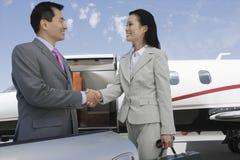 Apretón de manos del negocio en el campo de aviación Imagen de archivo libre de regalías
