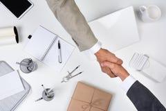 Apretón de manos sobre el escritorio Imagen de archivo libre de regalías