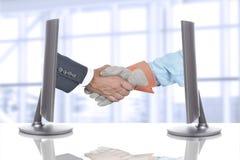 Apretón de manos sobre el escritorio en oficina de negocios Imagenes de archivo