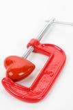 Apretón del tornillo y corazón rojo Imagen de archivo libre de regalías