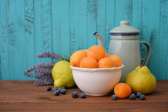 Apricot, blueberry and pear. Apricots in bowl with fresh pear and blueberry on wooden background Royalty Free Stock Photography