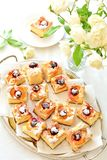 Apricot and cherry sponge cake. Divided in pices on a tray. Light background and white roses decoration royalty free stock image