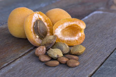 Apricot fruit cut open with pips and kernels in the foreground. Apricot fruit, stones and kernels on a wooden platform in natural light Stock Photography