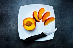 Apricot. Half an apricot and four slices on a plate and a small knife on the side Royalty Free Stock Photography