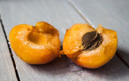 Apricot halves with a nucleus on a wooden background. Apricot halves with a nucleus on wooden background royalty free stock image