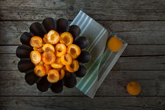 Apricot Halves With Sugar Syrup Above View. Apricot halves with sugar syrup in black bowl, above view stock image