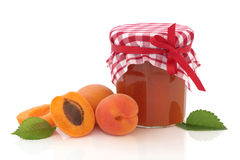 Apricot Jam. In a jar with apricots whole and in half with leaf sprig, over white background Royalty Free Stock Photography