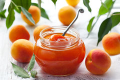 Apricot jam. In jar and fresh fruits with leaves stock photo