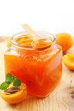 Apricot jam. In jar and fresh fruits on wooden background royalty free stock image