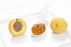 Apricot jam, an apricot and a half on a wite plate Stock Photography