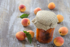 Apricot jam in closed glass jar and fresh fruits, on wooden gry background Royalty Free Stock Photo