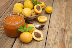 Apricot jam. Fresh apricot jam in a jar with mint and apricot fruits on wooden table royalty free stock photo