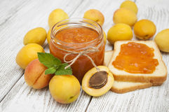 Apricot jam. Fresh apricot jam in a jar with mint,with sandwiches and apricot fruits on wooden table stock image