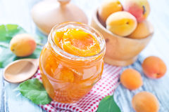 Apricot jam. In glass bank and on a table Royalty Free Stock Photography