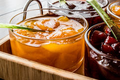 Apricot Jam in glass bowl with spoon and various fruit marmalade Stock Photography