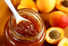 Apricot jam. Glass with apricot jam and fresh apricots Royalty Free Stock Photo