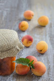 Apricot jam in closed glass jar and fresh fruits, on wooden gry background Royalty Free Stock Image