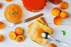 Apricot jam. In glass jar on an old white wooden table, top viewselective focus Stock Image