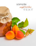 Apricot jam in a glass jar with ripe bright apricots on a white Stock Photos