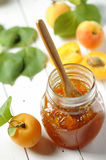 Apricot jam. In jar and fresh fruits on wooden background Stock Photos
