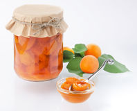 Apricot jam in a jar with a spoon. And chopped sprig whole apricot in the background Royalty Free Stock Images