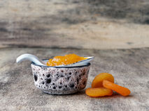 Apricot jam in little jar. Delicious and sweet apricot jam in a little ceramic jar with spoon and placed on wood Stock Photo