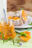 Apricot jam with mint. Jar with spicy apricot jam with mint. Bread and milk in the background royalty free stock photo