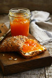 Apricot jam sandwich with sunflower seeds on rusted cutting board Royalty Free Stock Images