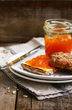 Apricot jam sandwich topped with sunflower seeds on white plate Royalty Free Stock Photos