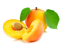 Apricot with leaves. Apricot whole both a half with leaves and a stone Stock Photos