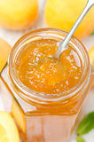 Apricot marmalade in a spoon close-up, vertical Stock Images