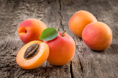 Apricot. Organic fruit with leaf on wooden background Royalty Free Stock Image