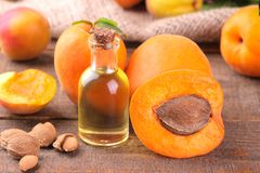Apricot seed oil next to apricots on a brown background stock photos