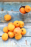 Apricot. Some fresh ripe raw juicy apricot on old wooden background Stock Image