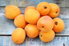 Apricot. Some fresh ripe raw juicy apricot on old wooden background Stock Photos