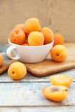 Apricot. Some fresh ripe raw juicy apricot on old wooden background Stock Images
