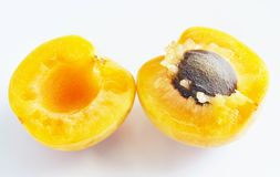 Apricot Split into Halves. Close up of a ripe apricot fruit cut into half with the stone royalty free stock image