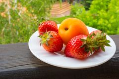 Apricot and Strawberries. On the white plate Royalty Free Stock Image