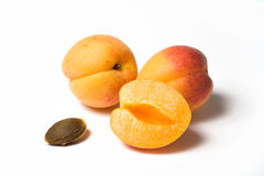 Apricots. Two whole apricots and a half on white Stock Photos