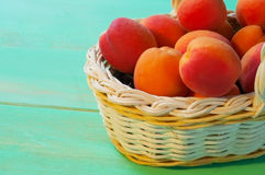 Apricots in basket on wooden background Royalty Free Stock Image