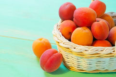 Apricots in basket on wooden background Stock Photos