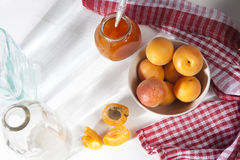 The Apricots in a bowl and jam in a jar on a white table with a red and white towel, handmade summer blanks Royalty Free Stock Photos