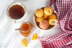 The Apricots in a bowl and jam in a jar on a white table with a red and white towel, handmade summer blanks Stock Image