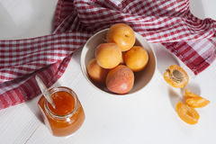 The Apricots in a bowl and jam in a jar on a white table with a red and white towel, handmade summer blanks Stock Images